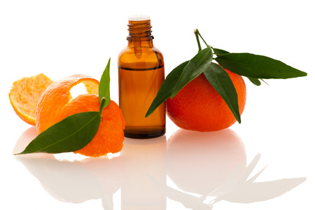 Essential oil of orange mandarin citrus fruit in little bottle decorated with mandarin peel, isolated over white background.
