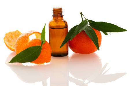 Essentiële olie van oranje Mandarijn citrusvruchten in kleine fles versierd met Mandarijn schil, geïsoleerd op witte achtergrond.