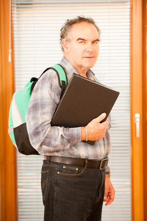lifelong: Older man representing lifelong learning. Man with school bag smiling as a gesture of happiness and joy of learning.