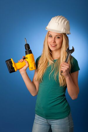 constructor: Woman with constructor helmet and tools happy to do tough work. Stock Photo