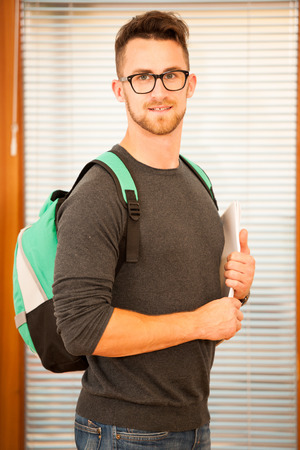 lifelong: Adult man representing lifelong learning. Man with school bag showing thumb up as a gesture of happiness and joy to study.
