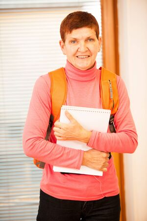lifelong: Older woman representing lifelong learning. Woman with school bag smiling and showing thumb up as a gesture of happiness and joy of learning. Stock Photo