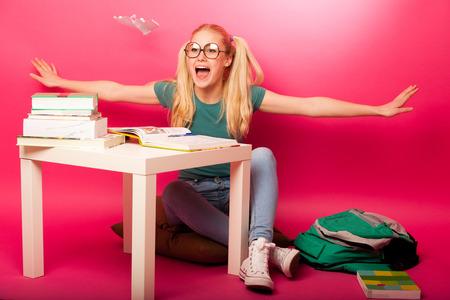 colegiala: Juguetona, traviesa colegiala con grandes gafas jugando con avi�n de papel, mientras que debe estudiar. Sentado detr�s del tabe lleno de libros. Foto de archivo