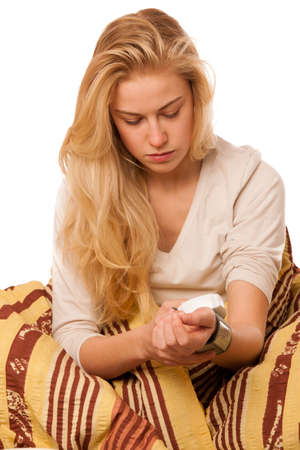 presure: Sick woman sitting on bad wrapped in a blanket feeling ill, has flu and fever, measuring blood presure.