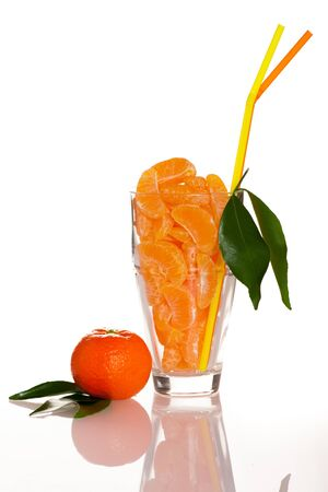 big leafs: Big glass filled with orange mandarin citrus fruit slices, decorated with straw and green leafs representing fresh natural juice. Stock Photo