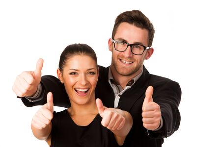 standing together: Confident business couple standing next to each other and showing thumbs up as a sign of success and pride. Conceptual image.