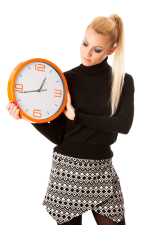 no rush: Calm smiling woman with big orange clock gesturing no rush, enough time to be punctual. Stock Photo
