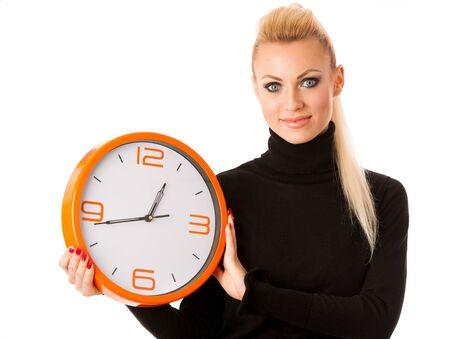 punctual: mujer sonriente en calma y con gran reloj de color naranja haciendo un gesto sin prisas, el tiempo suficiente para ser puntual.
