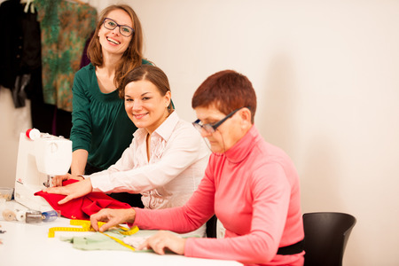 textile machine: Three women are sewing on handcraft workshop. They are teaching each other of sewing skills. Stock Photo