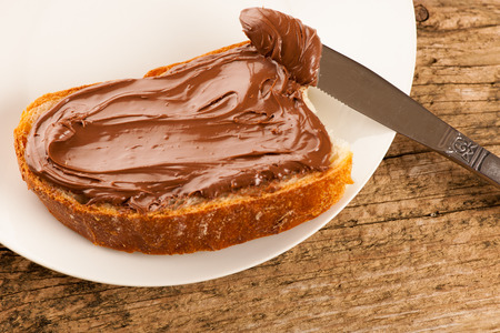 Slice of bread with sweet chocolate nougat spread on white plate.