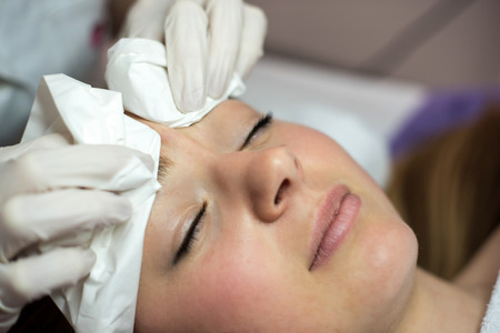 splotches: Young woman receiving beauty face therapy of cleaning pimple, acne.