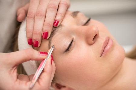 tweezing eyebrow: Plucking eyebrows with tweezer by beautician in beauty salon.
