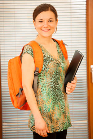 lifelong: Adult woman representing lifelong learning. Woman with school bag smiling as a gesture of happiness and joy to study. Stock Photo