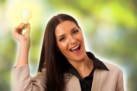 new idea: Woman holding light bulb above head as a sign of new idea.