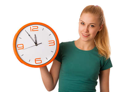lunchtime: Blonde woman holding big clock in hand smiling because it is five minutes to lunchtime, isolated over white.