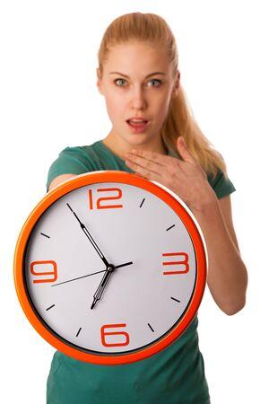 punctuality: Mujer rubia que sostiene el reloj grande en la mano, haciendo un gesto llegar tarde por la ma�ana, aislado m�s de blanco. Foto de archivo