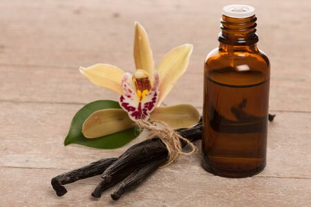 Vainas de vainilla, aceite de aromaterapia y flores de orquídeas en el fondo de madera Foto de archivo