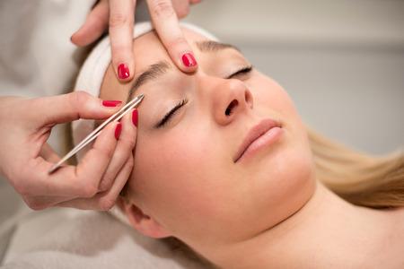 tweezing: Plucking eyebrows with tweezer by beautician in beauty salon.