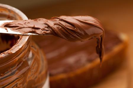 Couteau plein de douceur chocolat Nougat propagation sur bocal en verre. Banque d'images - 53080334
