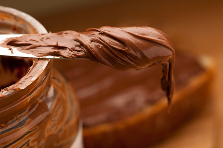 Knife full of sweet chocolate nougat spread on glass jar.