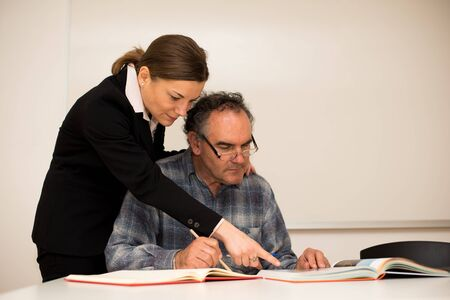 intergenerational: Young teacher explaining somethng to eldery man. Intergenerational transfer of knowledge. Stock Photo