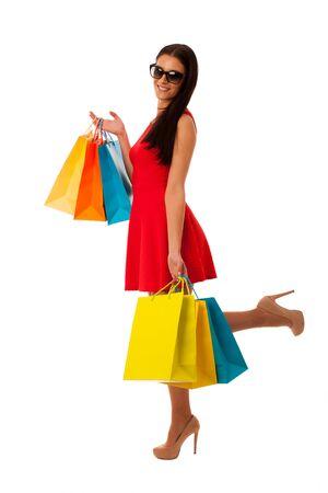 centro comercial: Mujer en el vestido rojo con bolsas de la compra excitados de la compra en el centro comercial. Foto de archivo