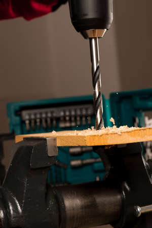 furniture hardware: Image of drilling hole with screwdriver in wood clamped in vice tool.