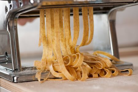 spelt: Making noodles with pasta machine from homemade spelt dough. Stock Photo