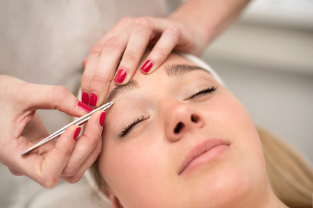 plucking: Plucking eyebrows with tweezer by beautician in beauty salon.