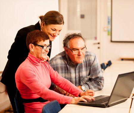 Mujer joven que enseña pareja de ancianos de conocimientos informáticos. la transferencia de conocimientos entre generaciones.