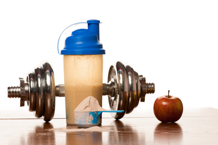 plastic scoop: Whey protein powder in scoop, dumbbell, meter tape and plastic shaker on wooden background.