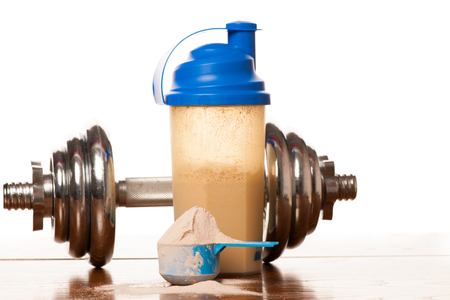 Whey protein powder in scoop, dumbbell, meter tape and plastic shaker on wooden background.