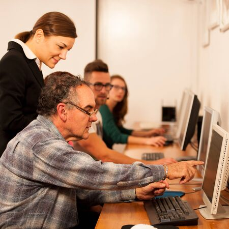 intergenerational: Group of adults learning computer skills. Intergenerational transfer of knowledge.