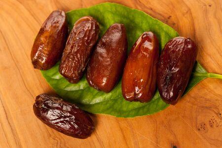 Sweet dried dates fruit on green leaf, mediterranean desert on wooden surface.