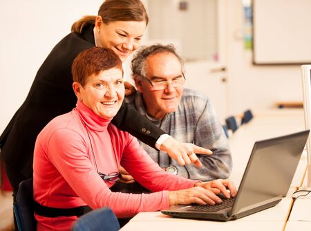 intergenerational: Young woman teaching elderly couple of computer skills. Intergenerational transfer of knowledge. Stock Photo