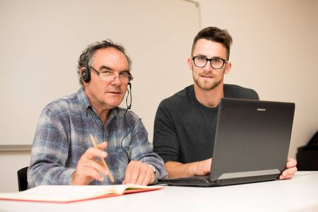intergenerational: Young man teaching eldery man of usage of computer. Intergenerational transfer of computer skills.