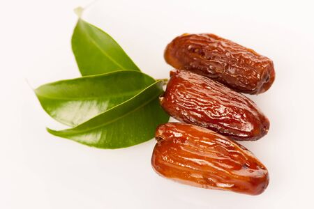 green dates: Sweet dried dates fruit on green leaf, mediterranean desert isolated over white.