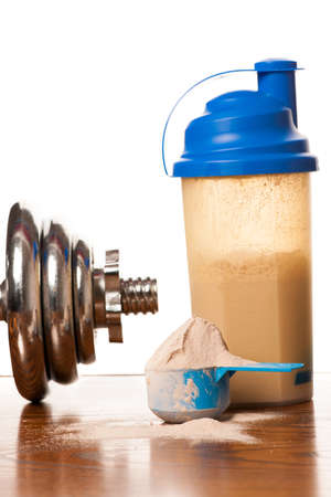 whey: Whey protein powder in scoop, dumbbell, meter tape and plastic shaker on wooden background.