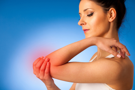 human's elbow: young woman having pain in injured elbow Stock Photo