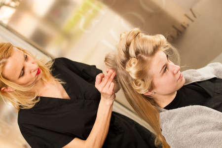 hair stylist: professional hair stylist at work - hairdresser  doing hairstyle to  beautiful young blonde customer in a professional studio