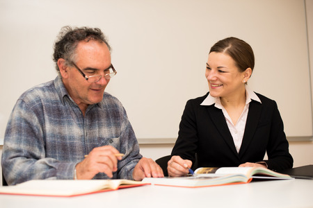 Young teacher explaining somethng to eldery man. Intergenerational transfer of knowledge. Stock Photo
