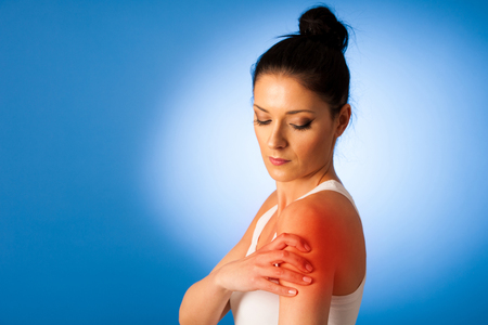 contracture: Beautiful woman having pain in her shoulder - injury Stock Photo
