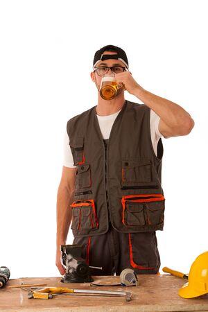 having a break: Handyman in work clothing having a break, drinkng beer isolated over white.