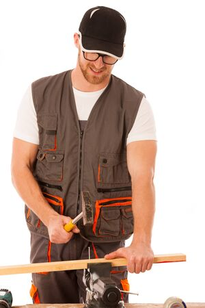 hammering: Handyman in work clothing hammering nail with hammer in home workshop isolated over white.