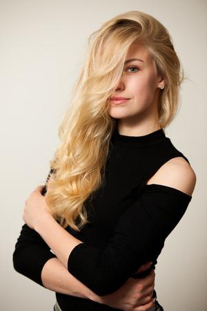 cabello rizado: Joven y bella mujer con el peinado magnífico que presenta sobre blanco Foto de archivo