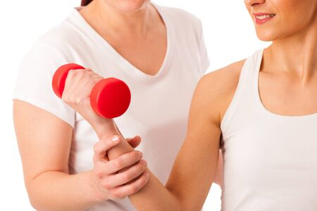 strenght: Physiotherapy - therapist doing arm  excercises with dumbbells for improving arm strenght and coordination  with a patient to recover  after injury Stock Photo