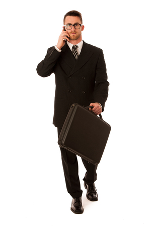confidently: Successful businessman in formal suit and briefcase, suitcase confidently standing isolated over white.