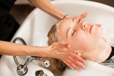 capelli biondi: Stilista di capelli sul lavoro - parrucchiere lavaggio dei capelli al cliente prima che fa acconciatura