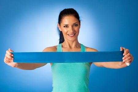 파란색 배경 위에 피트 니스 체육관에서 밴드와 함께 밖으로 작동하는 여자