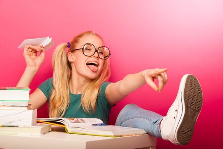 Playful, naughty schoolgirl with big eyeglasses throwing paper aeroplane sitting on floor behind the small table full of books.